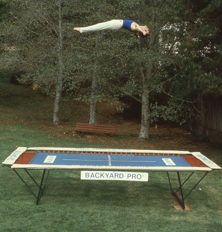 A World Trampoline Champion shows perfect form and control in a face up horizontal position over 24 feet high on his own personal Backyard Pro® trampoline. The trampoline is above ground on a green lawn with leafy trees in the background. This World Trampoline Champion is wearing white gymnastic pants and blue gymnastic top. The trampoline features our outdoor rated competition, high-performance blue string bed with white center markings. Our authoritative and expert 90 minute safety and instructional DVD is taught by this same World Trampoline Champion and is the best reviewed and most critically acclaimed  trampoline instructional & safety video ever made.