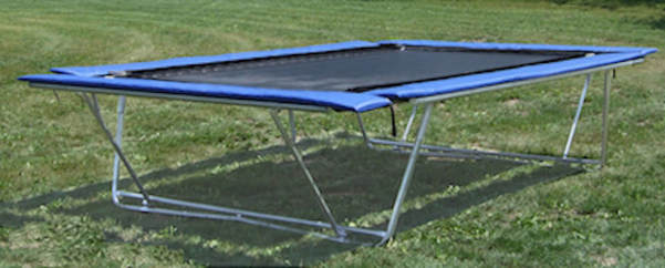 Backyard Pro trampoline is shown outside on a lawn in its aboveground mode. It can also convert to a ground-level installation.