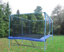 A Backyard Pro® trampoline sits above ground on a green lawn with evergreen trees and bushes in the background. It has blue pads with a black standard outdoor bed. Around the periphery of the trampoline is an attached safety enclosure net which is an optional accessory that we offer.
