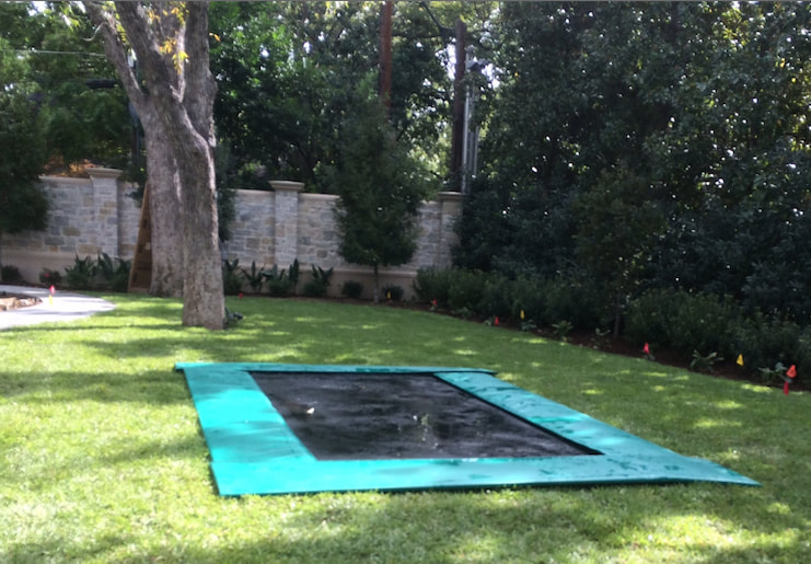 A Backyard Pro® Trampoline featuring our standard all-around outdoor black bed (also called the mat), stainless steel high performance springs, and extra-wide light green colored safety pads around the edge is installed at ground level on a green lawn. The extra-wide safety pads fully cover the springs and frame giving installation a very plush appearance. All that can be seen is the safety pads surrounding the black bed or mat. The lawn is beautiful and upscale with large trees and a hand built stone wall in the background.