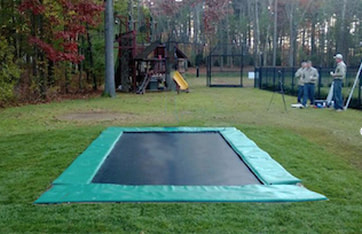 A Backyard Pro® Trampoline featuring our standard all-around outdoor black bed (also called the mat), stainless steel high performance springs, and extra-wide light green colored safety pads around the edge is installed at ground level on a green lawn. The extra-wide safety pads fully cover the springs and frame giving installation a very plush appearance. All that can be seen is the safety pads surrounding the black bed or mat. The lawn is on a beautiful upscale estate with large trees in the background. There is a wrought-iron fence around the lawn. In the background three men are standing by the fence. To the rear background is an iron gate leading to the lawn with the trampoline is placed.