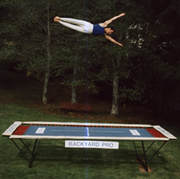 A World Trampoline Champion shows perfect form and control in a face forward sideways horizontal position over 20 feet high on his own personal Backyard Pro® trampoline. The trampoline is above ground on a green lawn with leafy trees in the background. This World Trampoline Champion is wearing white gymnastic pants and blue gymnastic top. The trampoline features our outdoor rated competition, high-performance blue string bed with white center markings. Our authoritative and expert 90 minute safety and instructional DVD is taught by this same World Trampoline Champion and is the best reviewed and most critically acclaimed  trampoline instructional & safety video ever made.
