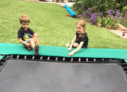 Two young children, about five years old, are sitting on their Backyard Pro® trampoline installed at ground level. In the background are long some flowers and a practice balance beam. This photo shows that the Backyard Pro installed at ground level is an ideal platform for even young gymnasts to play and practice on.