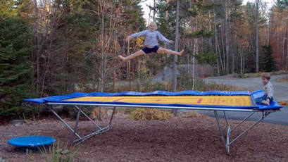 A Backyard Pro® trampoline with a yellow competition bed and high performance stainless steel springs sits above ground in a clearing in a wooded area. An eight-year-old girl is doing a splits jump with an even younger boy observing from the from the built-in blue padded observation deck of the trampoline.