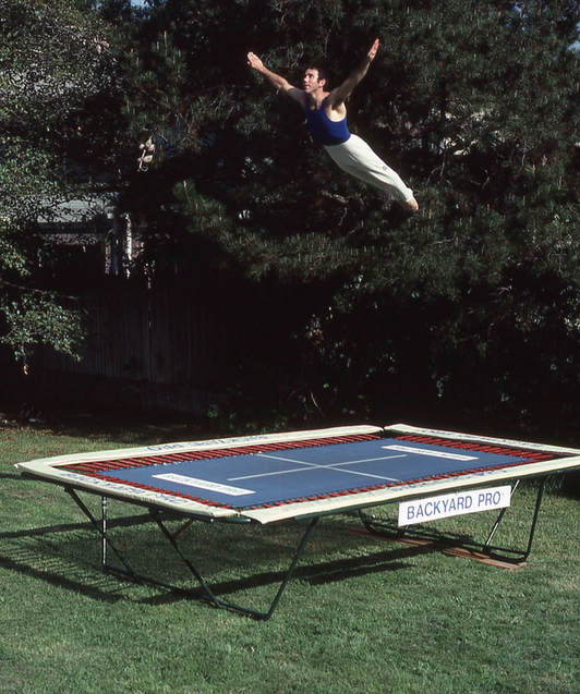 A World Trampoline Champion performs a horizontal swan dive with perfect artistic form. He is high above his own personal Backyard Pro® High-Performance Gymnastic and Sports Training Trampoline. The trampoline is outside on green grass with leafy trees in the background. The trampoline has an outdoor rated blue competition high performance string fly bed and tan safety pads. The World Trampoline Champion is wearing a navy blue gymnastic top with white gymnastic pants.