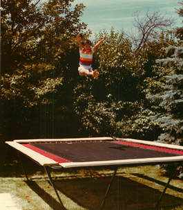 A young 10-year-old gymnast bounces 10 feet high in a sitting position above her Backyard Pro® gymnastics training trampoline.showing perfect form & control. Her Backyard Pro® trampoline is above ground on her lawn outside with trees and bushes in the background. In addition to fun and recreation, every Backyard Pro® trampoline is an ideal sports training platform especially for gymnastics and other aerobatic type sports.